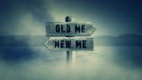 Vecchio segno di legno su un mezzo di una strada trasversale con le parole vecchie me o nuovo me