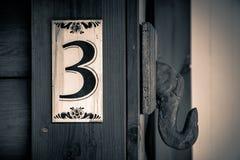 Vecchio segno di numero dell'appartamento sulla parete di legno con il numero tre su  Immagine Stock Libera da Diritti