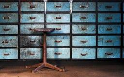 Vecchio sgabello sulla priorità bassa dei cassetti Fotografia Stock Libera da Diritti