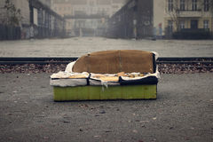 Vecchio sofà in una città sporca Immagini Stock