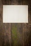 Vecchio strato di carta su fondo di legno Fotografia Stock