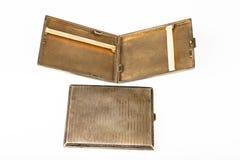 Vecchio tabacco-tubo del metallo su una tavola bianca Le sigarette antiquate imballano fotografia stock