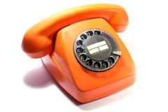 Vecchio telefono arancione isolato su priorità bassa bianca fotografia stock libera da diritti