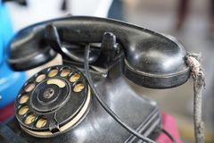 Vecchio telefono nero antico d'annata con il disco rotatorio fotografia stock libera da diritti