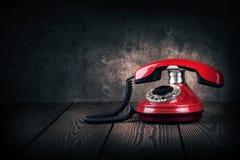 Vecchio telefono rosso su una tavola di legno fotografie stock