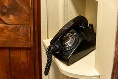Vecchio telefono rotatorio nella vecchia posizione di tenuta, sedentesi nell'angolo nel corridoio fotografia stock libera da diritti