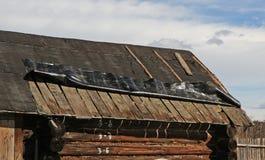 Vecchio tetto coperto di materiale di tetto, necessitante la riparazione Fotografia Stock