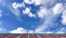 Vecchio tetto del ferro con il fondo del cielo delle nuvole Immagine Stock