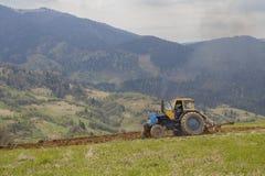 Vecchio trattore che ara la terra negli altopiani Fotografia Stock Libera da Diritti