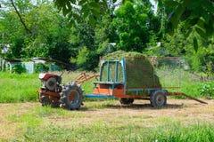 Vecchio trattore con erba o fieno sul rimorchio veicolo di agricoltura Fotografie Stock
