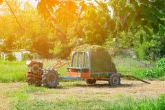Vecchio trattore con erba o fieno sul rimorchio veicolo di agricoltura Immagini Stock