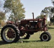 Vecchio trattore rosso del paese su paesaggio pittoresco fotografia stock