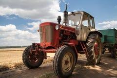 Vecchio trattore sul campo, contro un cielo nuvoloso Fotografia Stock Libera da Diritti