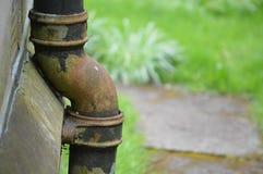 Vecchio tubo di scarico stagionato su una parete della chiesa Fotografia Stock Libera da Diritti