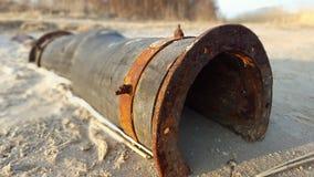 Vecchio tubo per fognatura arrugginito sulla riva di un fiume con fondo vago Fotografie Stock Libere da Diritti