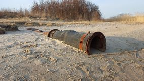 Vecchio tubo per fognatura arrugginito sulla riva v2 di un fiume Fotografie Stock Libere da Diritti