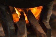 Vecchio vaso che sta sulla stufa bruciante di legno Fotografia Stock
