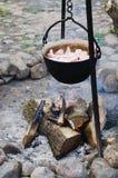 Vecchio vaso per la cottura sopra un fuoco di accampamento Fotografie Stock