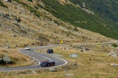 Vecchio viaggio di automobili del cabriolet sulla strada di bobina in montagne di Carpathians Immagini Stock