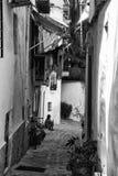 Vecchio vicolo Mediterraneo tipico fra il vecchi nero delle case e wh Fotografia Stock