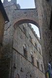 Vecchio vicolo nella vecchia città di Volterra in Italia con l'arco di pietra fotografia stock libera da diritti