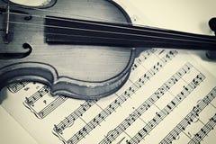 Vecchio violino e note musicali Fotografia Stock