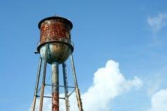 Vecchio watertower arrugginito contro cielo blu Immagine Stock