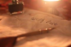 Vecchio wishlist con la piuma a penna ed inchiostro e candela sulla tavola di legno immagine stock libera da diritti