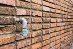 Vecchio woth del tubo dell'acqua il muro di mattoni Fotografia Stock Libera da Diritti