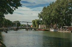 Vecht flod med bron, fartyg på bankerna och tegelstenhus på en solig dag i Weesp Royaltyfria Bilder