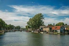 Vecht flod med bron, fartyg på bankerna och tegelstenhus på en solig dag i Weesp Arkivfoton