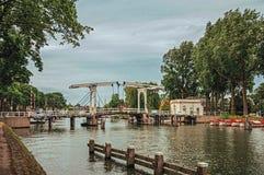 Vecht flod med bron, fartyg på bankerna och träd på en solig dag i Weesp Arkivbild