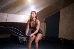 Vechtend kabelsmeisje bij het gepaste lichaam van de gymnastiektraining oefening Stock Foto's