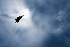 Vechtersvliegtuig backlit door de zon in een donkere, bewolkte hemel Royalty-vrije Stock Fotografie