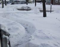 Vecindad nevada con la calzada traspalada después de una tormenta y de un Durin de la nieve fotos de archivo