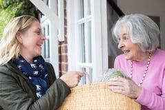 Vecino femenino que ayuda a la mujer mayor con compras foto de archivo libre de regalías