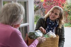 Vecino femenino que ayuda a la mujer mayor con compras imagen de archivo