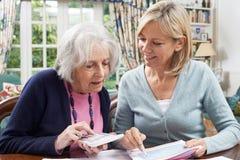 Vecino femenino que ayuda a la mujer mayor con finanzas nacionales foto de archivo