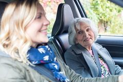 Vecino femenino que da a mujer mayor una elevación en coche imagen de archivo libre de regalías