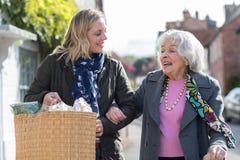 Vecino maduro que ayuda a la mujer mayor a Carry Shopping imagen de archivo libre de regalías