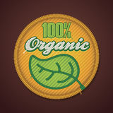 Vector 100% organic fabric badge. Detailed icon representing fabric badge with embroidered 100% organic text stock illustration