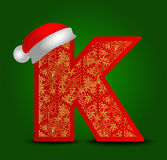 Vector alphabet letter K with christmas hat and gold snowflakes Royalty Free Stock Photo