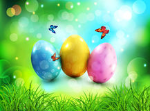 Vector background. Easter eggs in green grass with white flowers. Butterflies on blue, blurred , natural background Royalty Free Stock Photo