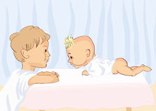 Vector Brothers. A little boy standing at the table and smiles lies a newborn little brother Stock Image