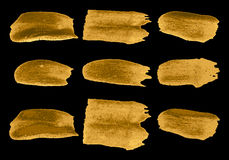 Vector brush stroke gold paint abstract on black background set Royalty Free Stock Images