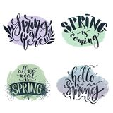 Vector calligraphic set. Spring related phrases set. Spring is here, coming, hello and all we need is spring words on. Colored backdrops vector illustration