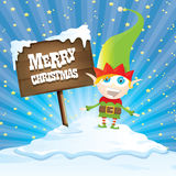 Vector cartoon merry Christmas elf on north pole. Vector cartoon cute merry Christmas elf standing on winter snow landscape near wooden sign board with greeting Stock Photos