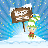 Vector cartoon merry Christmas elf on north pole. Vector cartoon cute merry Christmas elf standing on winter snow landscape near wooden sign board with greeting Stock Photo