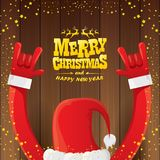 Vector cartoon Santa Claus rock n roll style with golden calligraphic greeting text on wooden background with christmas Royalty Free Stock Photography