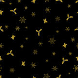 Vector Christmas seamless pattern from golden snowflakes, bells and berry on black background. Royalty Free Stock Photos
